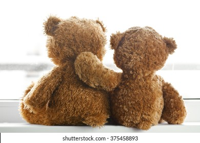 Two teddy bears sitting back