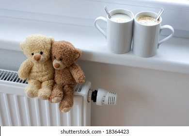 Two teddy bears sitting on radiator in home, with coffee cups on windowsill