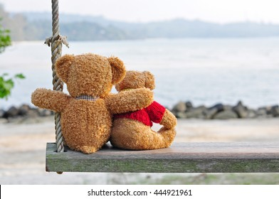 Two teddy bears sitting on the wooden swing with nature background. Concept about love and relationship.