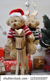 Two Teddy Bears with in a striped sweater & a Santa Claus cap & another one with in a striped sweater are riding a wooden hobbyhorse on a background of a Christmas tree & boxes with Christmas presents