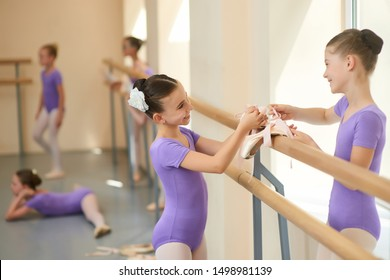 Two teen ballerias talking in ballet studio. Two young happy ballet dancers communicate to each other and smile. Beautiful teen friends.