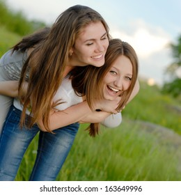 Two Teen Girl Friends Laughing in spring or summer outdoors