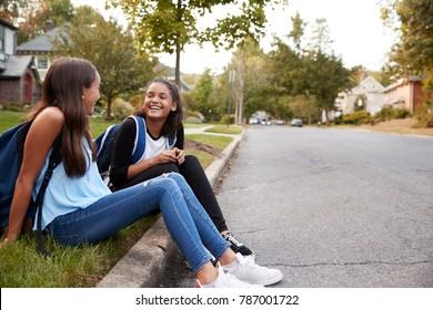 Two teen girlfriends sit talking at the roadside