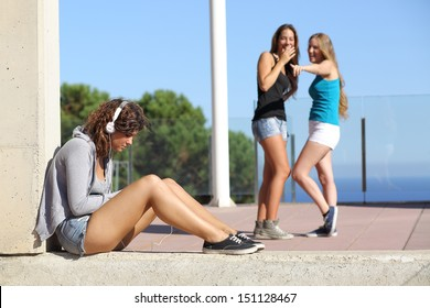 Two teen girls bullying and making fun and pointing another one