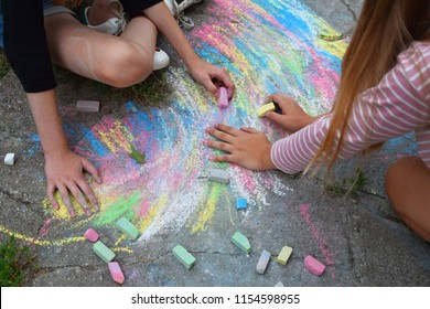 Two teen girls drawing with chalk crayons outdoors. Child hands on abstract colorful drawing and chalk crayons on old grunge cracked concrete sidewalk.