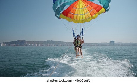 Two teen girls are excated before take off at para sailing with a rope pulled by a boat