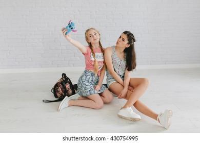 Two teen girls on the skateboard make selfie.