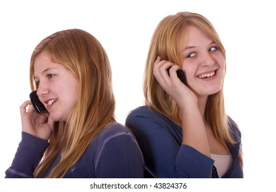 Two teen girls on their cell phone, talking and using SMS