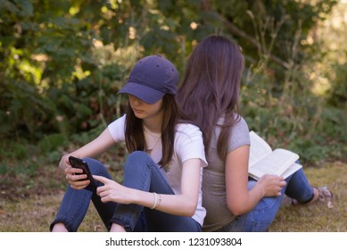 Two teen girls, one reading a book and the other on a phone