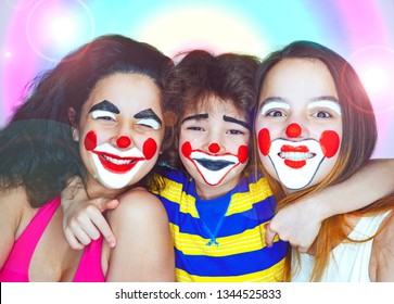 Two teen sisters and a little brother in the role of clowns posing bright colorful background. Family affection concept.