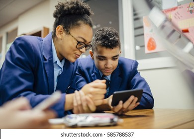 Two teen students are sneakily looking at a smart phone together during lesson time.