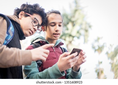 Two teenage boys with backpack on city street