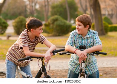 Two teenage boys having fun in the park riding bicycles.