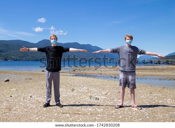 Two teenage boys standing at a beach showing social distancing using raised arms to show a two meter distance.