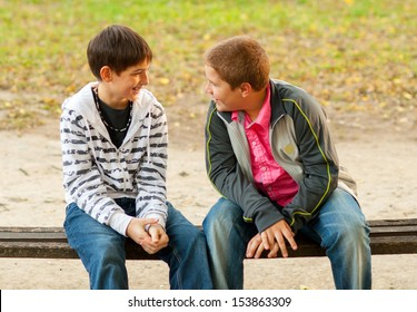 Two teenage friends talking while sitting on the bench in the park
