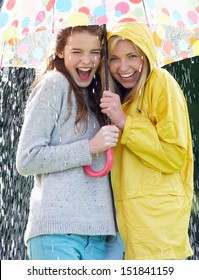 Two Teenage Girl Sheltering From Rain Beneath Umbrella