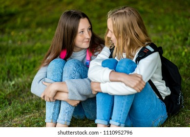 Two teenage girl. Summer in nature. They are sitting on the grass. Communicate with each other. He talks intimate conversation. Best friends. Privacy from adults.