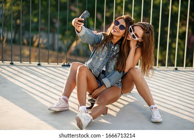 Two teenage girlfriends in hipster outfit sitting on skateboard at the park and make selfie photo on smartphone. Happy friendship and active lifestyle.