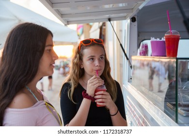 Two teenage girls buy smoothie in a food truck at dusk