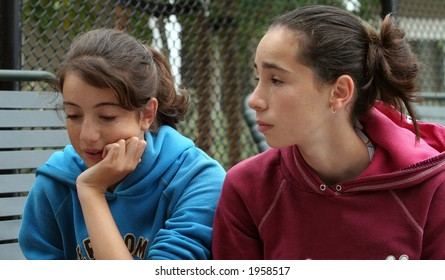 Two teenage girls discussing their problems outdoors
