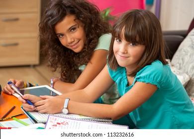 Two teenage girls doing homework at home.