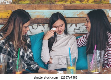 Two teenage girls friends supporting and consoling crying young woman - friendship concept with young millennial girls at restaurant talking about couple problems – relationship problems of teenagers