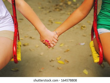 Two teenage girls holding hands on beautiful autumn day.