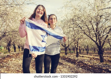 Two teenage girls are holding an Israeli flag outdoors
