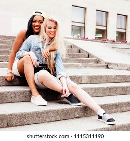 Two teenage girls infront of university building smiling.