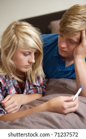 Two Teenage Girls Lying On Bed Looking At Pregnancy Testing Kit
