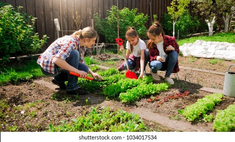 Two teenage girls with mother working in backyard garden