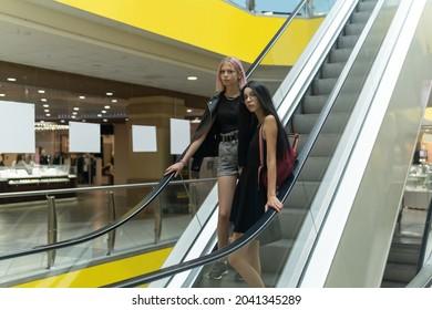 two teenage girls on the escalator in the mall