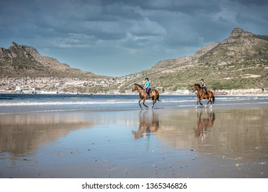 Two teenage girls on horseback cantering in the water at low tide on the beach under a cloud sky with a beautiful mountain in the background and reflections of themselves in the water on the shore