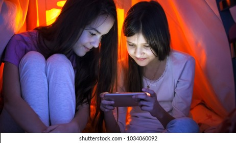 Two teenage girls in pajamas browsing internet on mobile phone at night - Shutterstock ID 1034060092