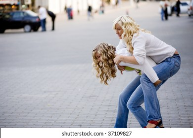 Two teenage girls playing in city