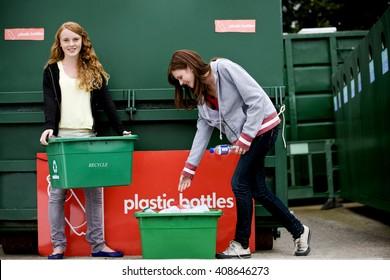 Two teenage girls recycling plastic bottles
