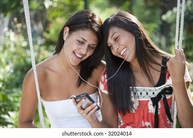 Two teenage girls sharing an MP3 player and smiling