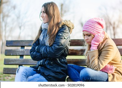 Two teenage girls sit with their backs to each other and do not talk because they quarreled