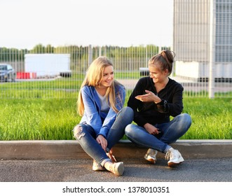 Two teenage girls sitting together outdoors