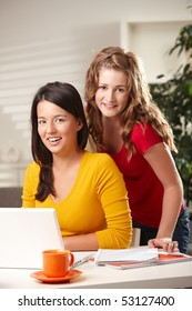 Two teenage girls smiling at camera with laptop on table at home.