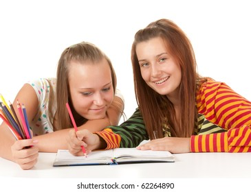 Two teenage girls smiling and reading book  isolated on white