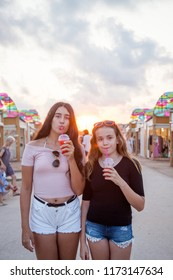 Two teenage girls stroll through an open-air market and have a refreshing red drink.