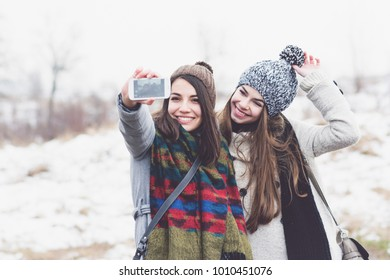 Two teenage girls taking a selfie smiling outdoors in winter on snowy day