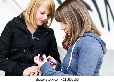 Two teenage girls using smart phone