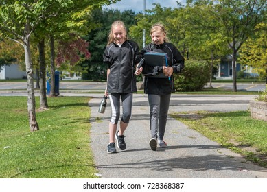 Two teenage girls walking to school happy and laughing, Canada.