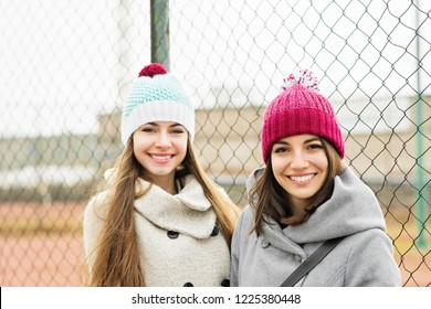 Two teenage girls in winter outfits and knitted beanie hats, smiling, outdoors in autumn or winter. Closeup, medium retouch, natural lighting.