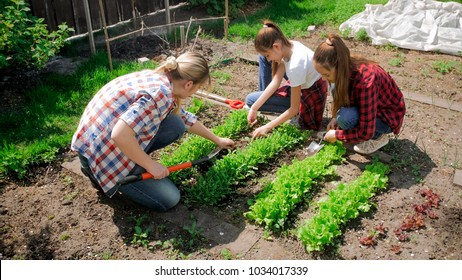 Two teenage girls with young mother taking care of backyard garden
