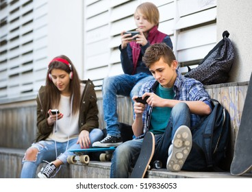 Two teenage males and their girlfriend relaxing with mobile phones outdoor. Focus on guy