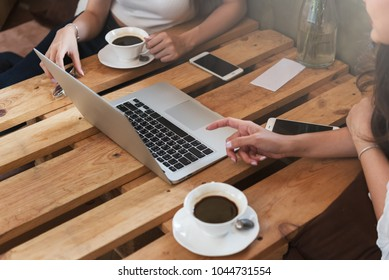 Two teenage women meet in coffee shop use laptop and smartphone play social media together in afternoon, life style of new teenager