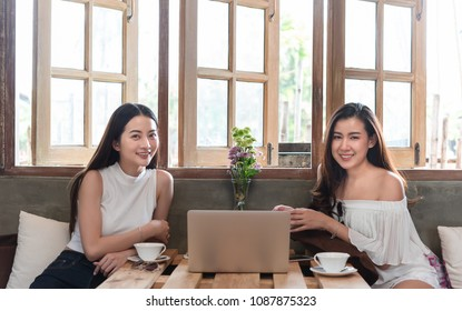 Two teenage women meet in coffee shop use smartphone and laptop play social media together in afternoon, life style of new teenager